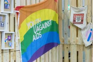"""Flagge mit Regenbogenfarben und Aufschrift """"Youth Against AIDS"""""""