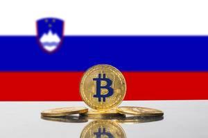 Flagge von Slowenien mit vier goldenen Münzen der Kryptowährung Bitcoin im Vordergrund