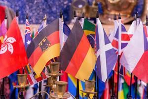 Flaggen von Deutschland und anderen Ländern aneinandergereiht hinter leerem Kerzenständer