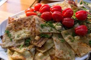 Flammkuchen mit Apfelmus und Fete-Käse, gestapelt auf einem weißen Teller