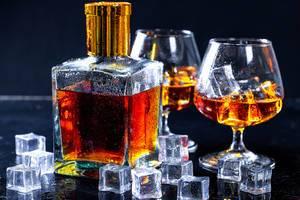 Flasche mit Brandy und zwei mit Likör und Eiswürfeln gefüllte Gläser vor dunklem Hintergrund