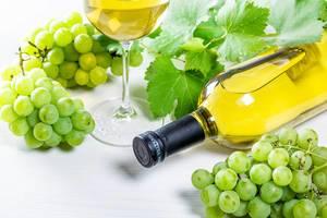 Flasche Wein liegt auf einem Tisch, zwischen Weintrauben und grünen Blättern