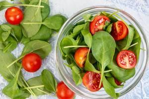 Flat lay above Baby Spinach wirh Cherry Tomato
