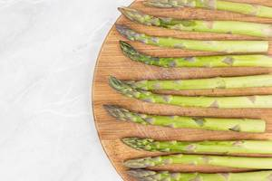 Flat lay above Fresh Asparagus on the wooden board