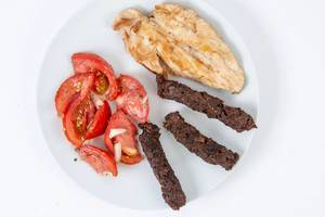 Flat lay above served grilled Chicken Breasts with Kebabs and Tomatoes (Flip 2019)