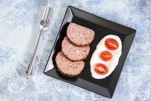 Flat lay above Served Pork and Chicken Meat Loaf with Tomatoes