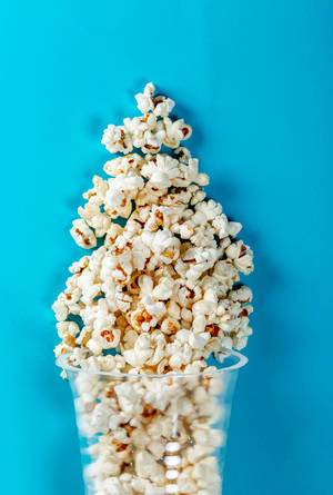 Flat lay of popcorn cup on a blue background. Top view