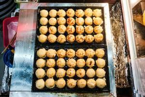 Flat lay of takoyaki balls on food tray (Flip 2019)