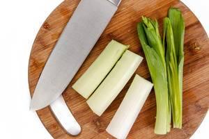 Flat-lay über frisch geschnittenem Lauch mit einem Messer auf einem Holzschneidebrett
