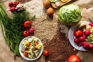 Flatlay Ansicht von veganem Essen und Getreide, auf Küchen-Backpapier ausgebreitet