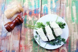 Flatlay auf einem hölzernen Tisch im Country-Stil: weißer Teller mit drei Stück Schafkäse und Petersilie, Salz- und Pfefferstreuer