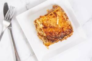 Flatlay einer gebackenen Lasagne auf einem weißen Teller neben Besteck