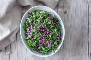 Flatlay eines Grünkohlsalats als Fitness-Vorspeise, auf einem Holztisch