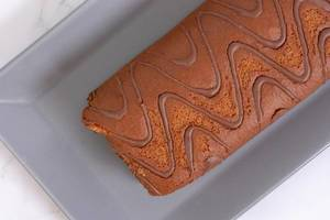 Flatlay eines Schokoladen-Biskuitkuchen auf einem Kuchentablett