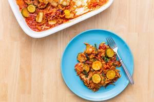 Flatlay mit Gemüse-Nudel-Auflauf auf einem blauen Teller