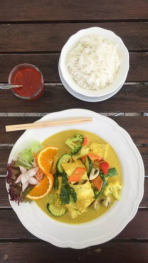 Flatlay of Asian, meatless dish with balanced vegetables and orange in a vegan curry turmeric sauce, next to a bowl of rice.