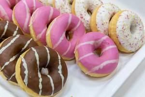 Flatlay shows three different donuts, with chocolate, coloured sprinkles and icing, on a white tray