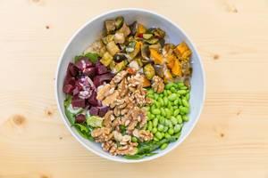 Flatlay von einem veganes Salat mit gegrilltem Gemüse, Edamame, Walnüsse und Soja-Sesam Soße in einer weißer Schale auf einem Holztisch