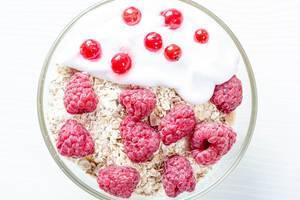 Flatlay von frischen Haferflocken mit Yoghurt, Himbeeren und Heidelbeeren auf weißem Holztisch
