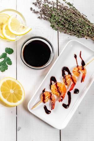 Flatlay von gegrillter Garnele auf weißem Teller mit Sojasoße, Zitrone und Koriander