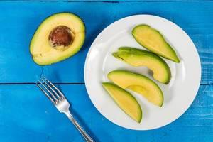 Flatlay von geschnittenen Avocadohälften auf einem blauen Tisch