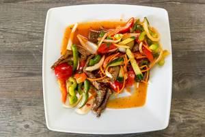 Flatlay zeigt ausgewogenes Thai-Essen mit Rindfleisch, Gemüse, Möhren, Chili, Zitronensaft, Zwiebeln, Koriander und Sellerie und Fischsoße