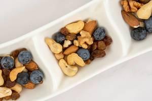 Flatlay zeigt blaue Beeren mit Rosinen, Mandeln, Walnüssen und Cashewkernen als gesundes Studentenfutter in weißen Schälchen zum snacken