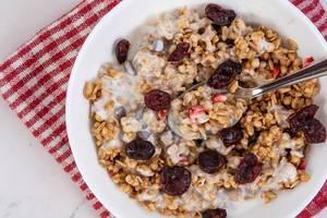 Flatlay zeigt ein Cornflakes-Frühstück, mit Schokoladenstücken, Erdbeeren und ganzen Cranberries