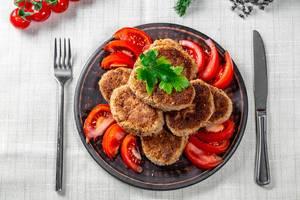 Flatlay zeigt ein Mittagessen aus Fleischschnitzel auf einem Holzteller, mit Messer und Gabel auf einer weißen Tischdecke