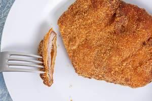 Flatlay zeigt ein paniertes Stück Fleisch auf einem weißen Teller