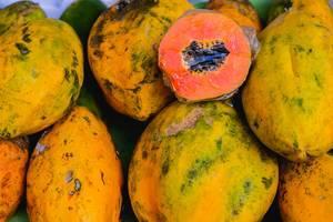 Flatlay zeigt eine aufgeschnittene Papaya-Frucht, die auf anderen Papayas liegt