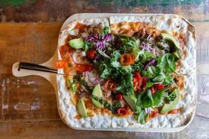 Flatlay zeigt Fladenbrot auf einem Holzbrett, belegt mit Käse, Chipotle-Tomatensauce, Salat, Chimichurri, und veganem Chili-Härkis aus Saubohnen