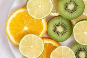 Flatlay zeigt Orangenscheiben, Limonen und Kiwis in Scheiben geschnitten, auf einem Teller