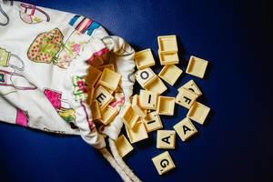Flatlay zeigt Scrabblesteine, die aus einem bunten Säckchen fallen