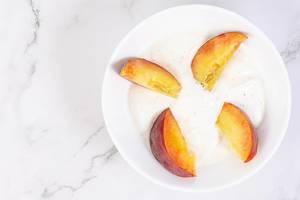 Flatlay zeigt vier geschnittene Pfirsichhälften auf einem kleinen Teller