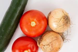 Flatlay zeigt Zwiebelknollen neben Tomaten und einer Salatgurke
