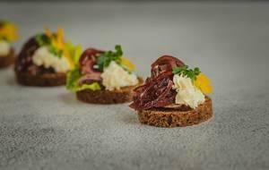 Fleisch-Canapé auf dunklem Brot und mit glasierten Zwiebeln - Nahaufnahme