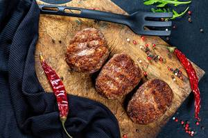 Fleisch-Schnitzel / Frikadellen mit Gewürzen und Chili auf einem Holzbrett auf dem Küchentisch