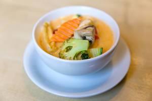 """Fleischlose und scharfwürzige Kokosmilchsuppe """"Tom Yum"""" mit  Tofu und frischem Gemüse, in einer weißen Suppenschüssel, als vegane Vorspeise"""