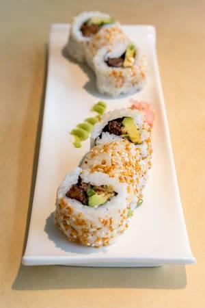 Fleischloses Sushi als japanisches, veganes Mittagessen mit gebackenem Tofu, Avocado, Röstzwiebeln, veganer Mayo und Kimchi-Sesam
