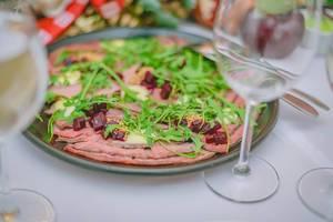 Fleischplatte mit Rucola und roter Bete auf gedecktem Tisch
