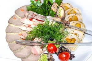 Fleischrollen mit getrockneten Aprikosen, Gemüse, gebackenem und geschnittenem Fleisch und frischen Kräutern