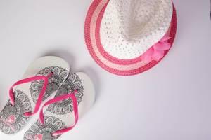 Flip-Flops und Sonnenhut als stilvolle weiß-pinke Accessoires für heiße Sommertage