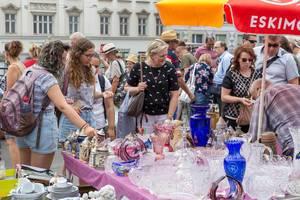 Flohmarkt-Besucher schauen sich Keramikgeschirr und Kristallgeschirr an einem Stand am Naschmarkt an