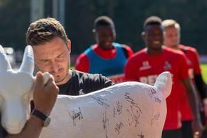 Florian Junge signiert eine Hennes VIII Figur