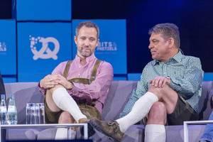 Florian Reuter und Dr. Carsten Breitfeld sitzen Beine verschränkt auf Sofa