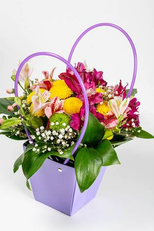 Flower arrangement in a gift box on white