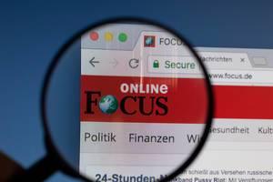 Focus Online Logo am PC-Monitor, durch eine Lupe fotografiert