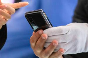 Folded Android Smartphone by Samsung: man holds the Galaxy Fold 5G dual-screen device