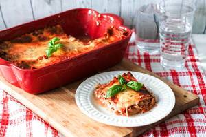Food Photo of Lasagna in a Ceramic Baking Pan with one Piece of Lasagna on a White Plate with Basil